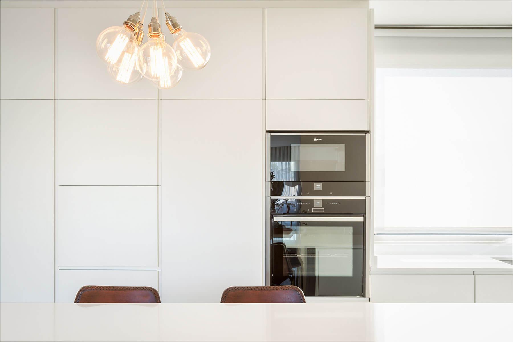Cocina blanca con isla en corian, con lámpara decorativa de bombillas - muebles de cocina