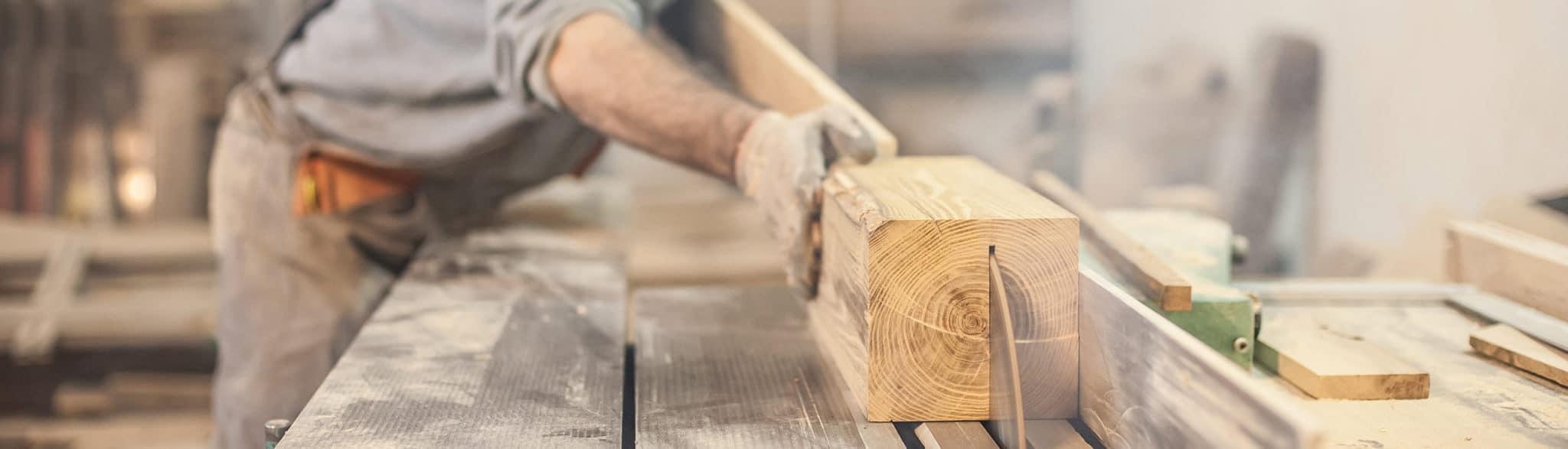Trabajador de Grupo Coeco serrando madera en la fábrica de muebles de cocina