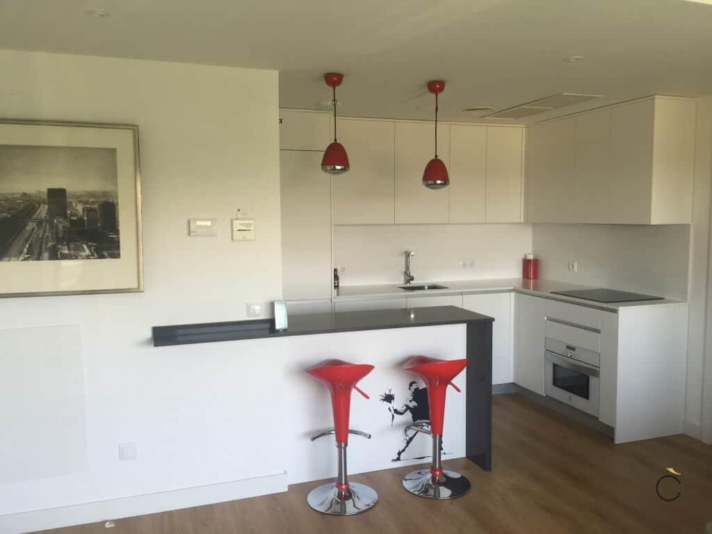Cocina blanca con península y taburetes rojos - cocinas blancas modernas