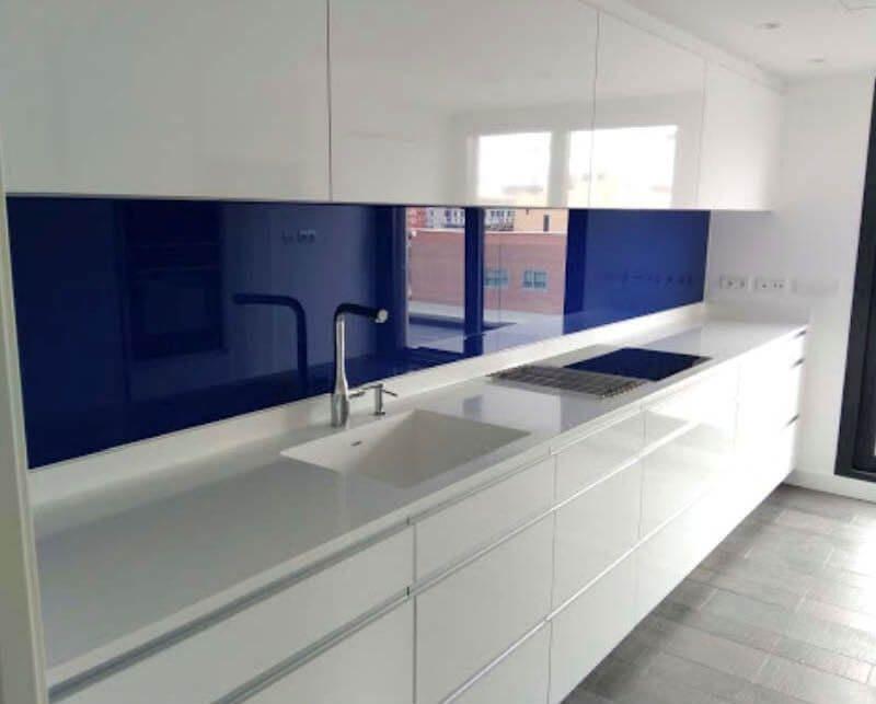 Cocina blanca Coeco de la serie Höst  con un peto de vidrio azul.