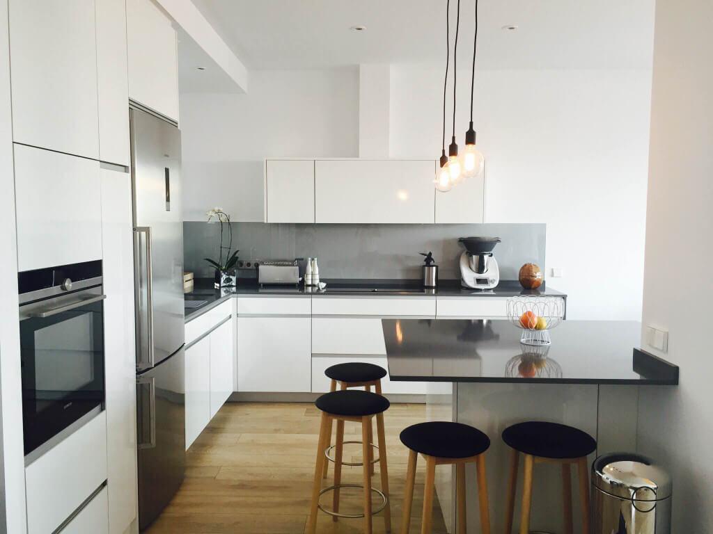 Cocina con península, muebles blancos y encima en negro - Cocinas con península