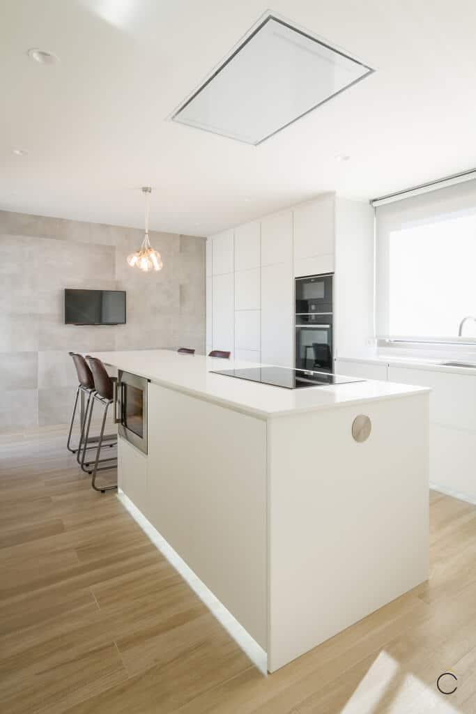 Cocinas modernas con isla de laca blanca mate con rtirador incluido y encimera Compac Stone vainilla