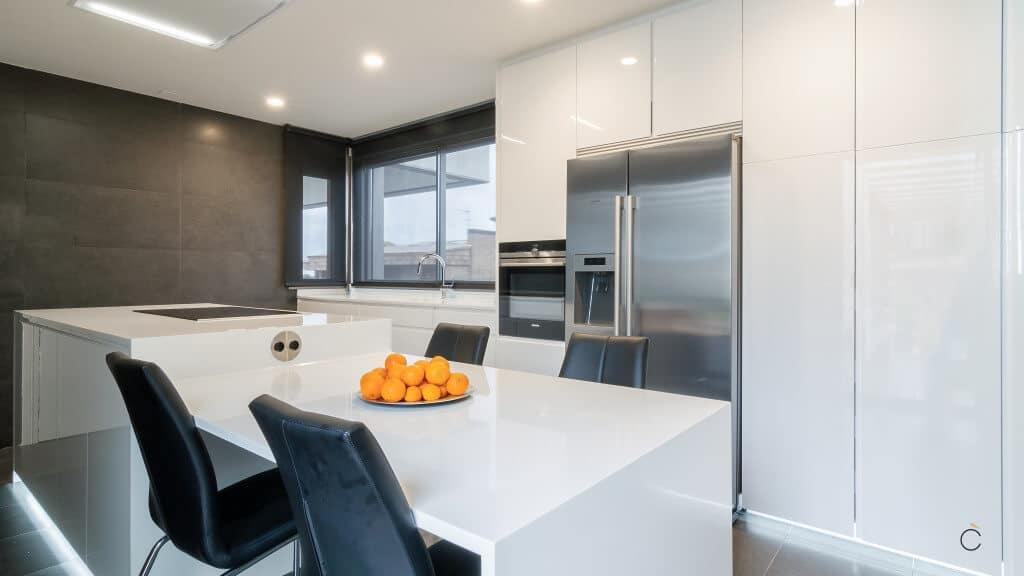 Cocinas modernas con isla de laca blanca mate con rtirador incluido y encimera Corian Dupont, glaciar White