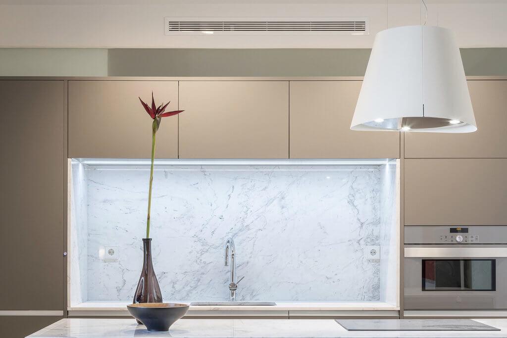 Cocina beige con encimera de marmol gris y campana decorativa - diseños de muebles de cocina