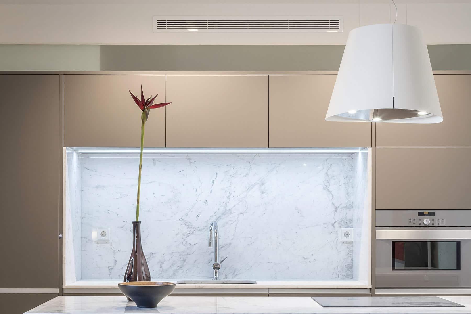 Cocina beige con encimera de marmol gris y campana decorativa - muebles de cocina