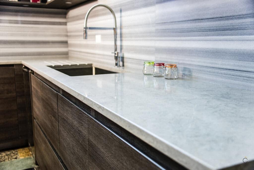 Cocina con muebles de madera oscura y encimera de mármol - cocinas de madera
