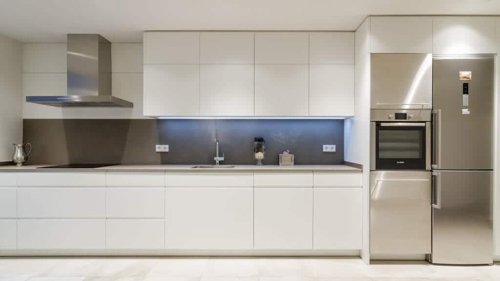Cocina lineal con gran capacidad de almacenaje blanca mate con encimera porcelanica - diseños de muebles de cocina