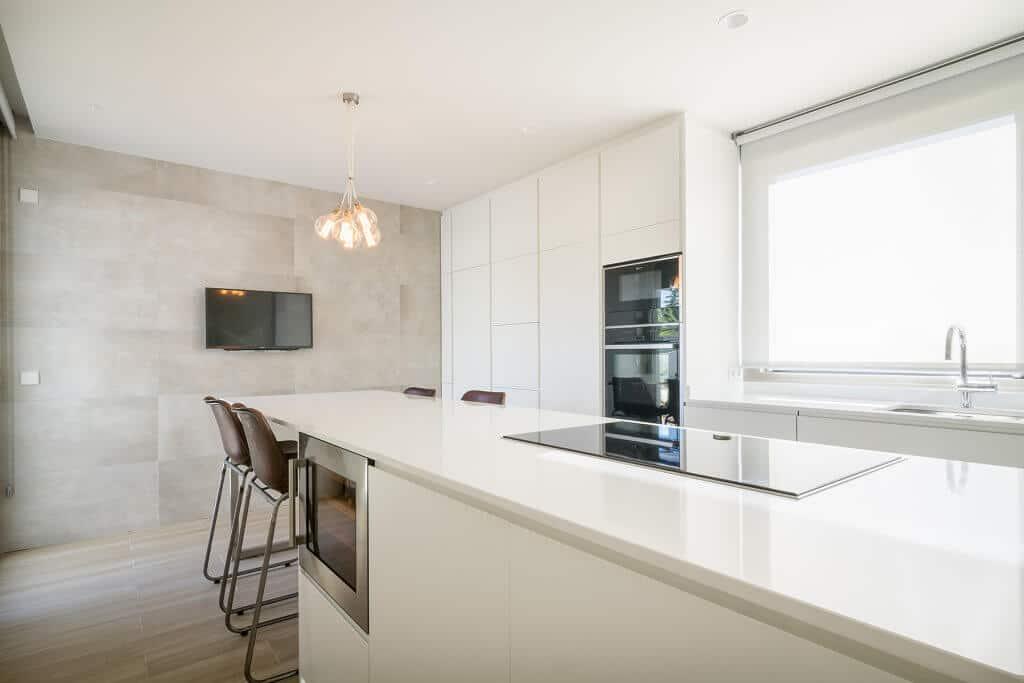 Cocina en blanco mate con isla y mesa de office - diseños de muebles de cocina