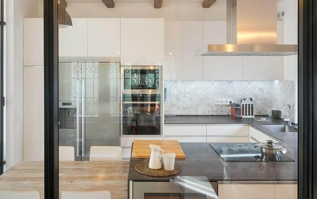 Cocina blanca con península en la que se combina el porcelánico y la madera natural - diseños de muebles de cocina