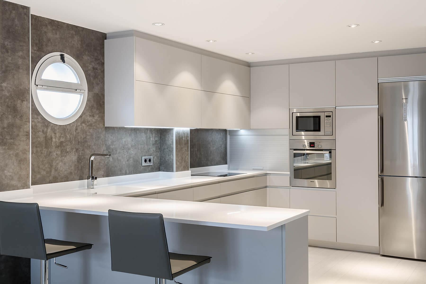 Cocina con península en colores grises con 2 taburetes en la península
