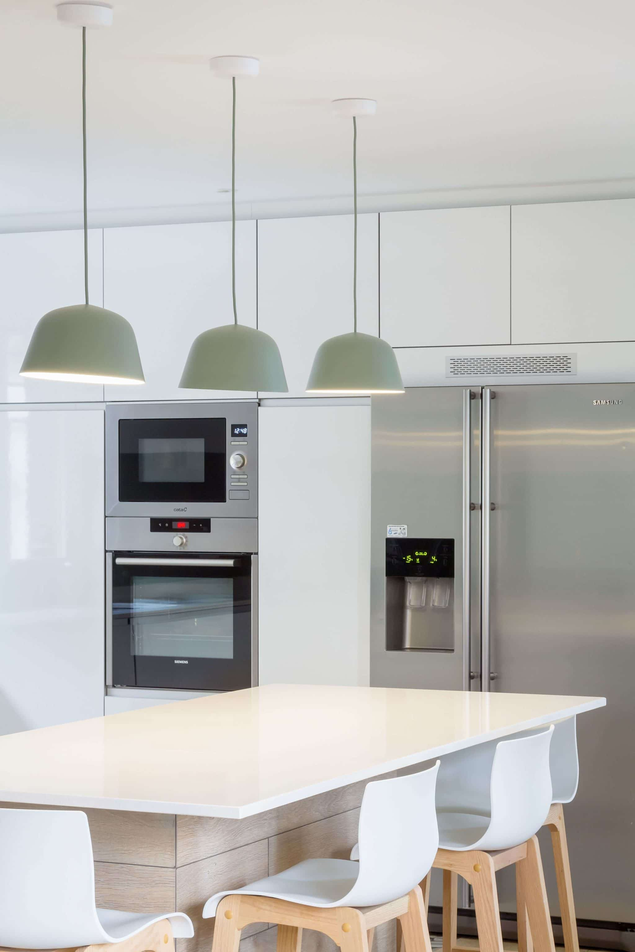 Detalle lamparas verdes en cocina con península verde menta y blanca