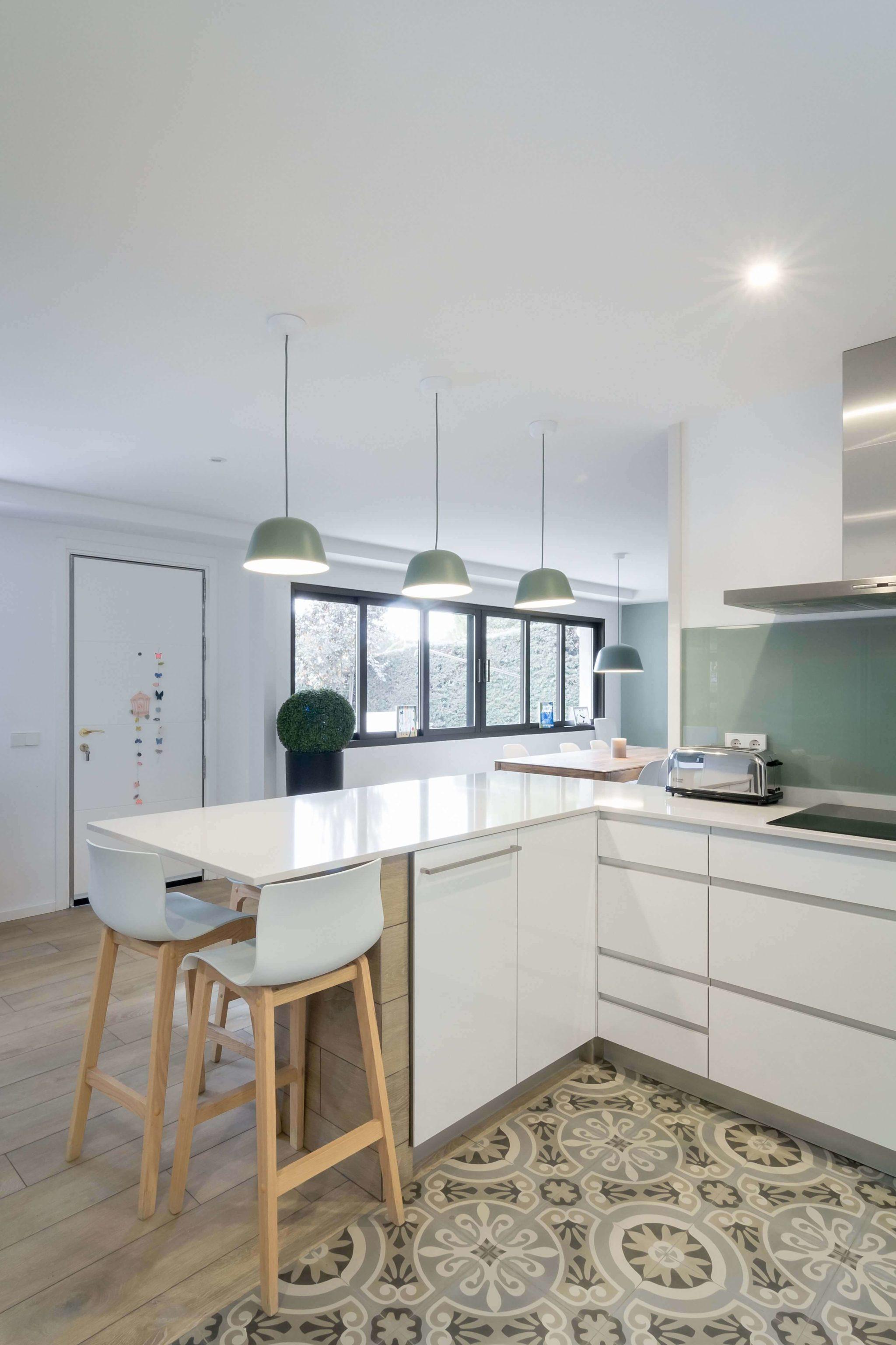 Cocina con península verde menta y blanca con taburetes altos