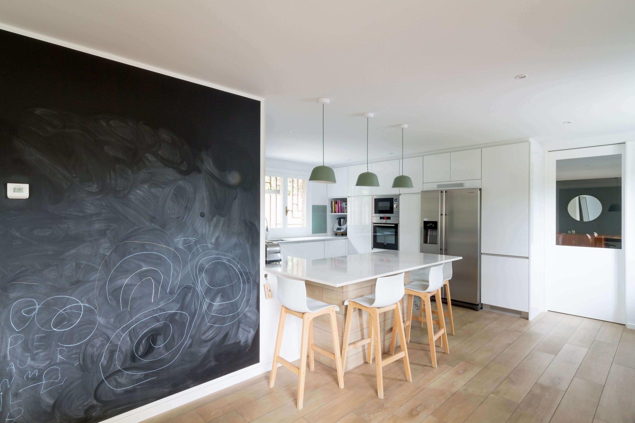 Cocina con península verde menta y blanca con pared de pizarra
