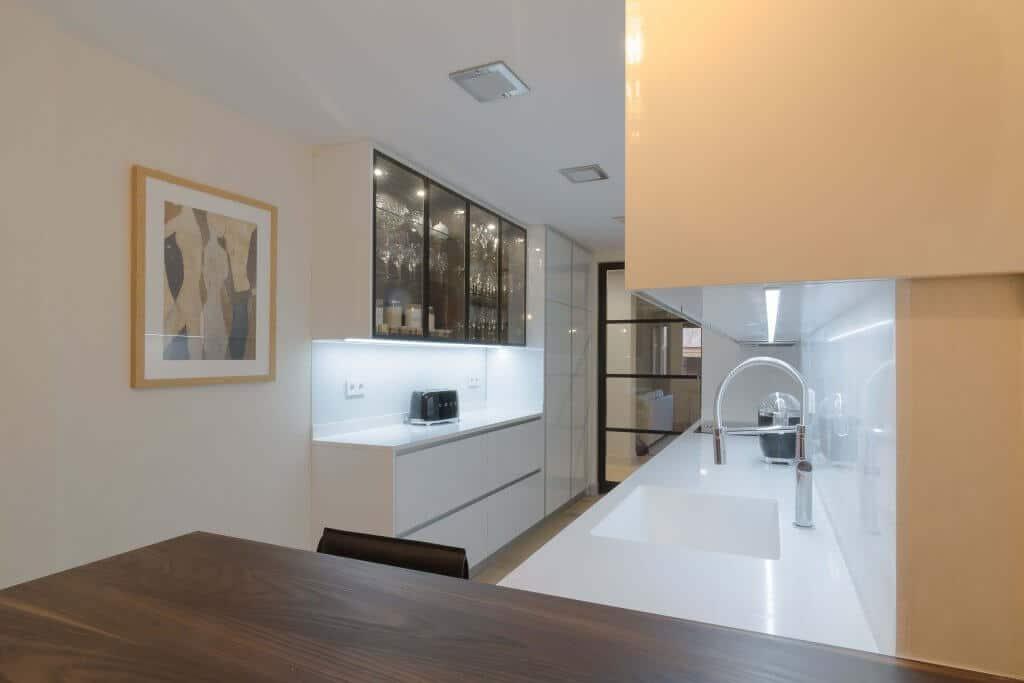 Cocina con dos frontales blanca con vitrina y península de madera