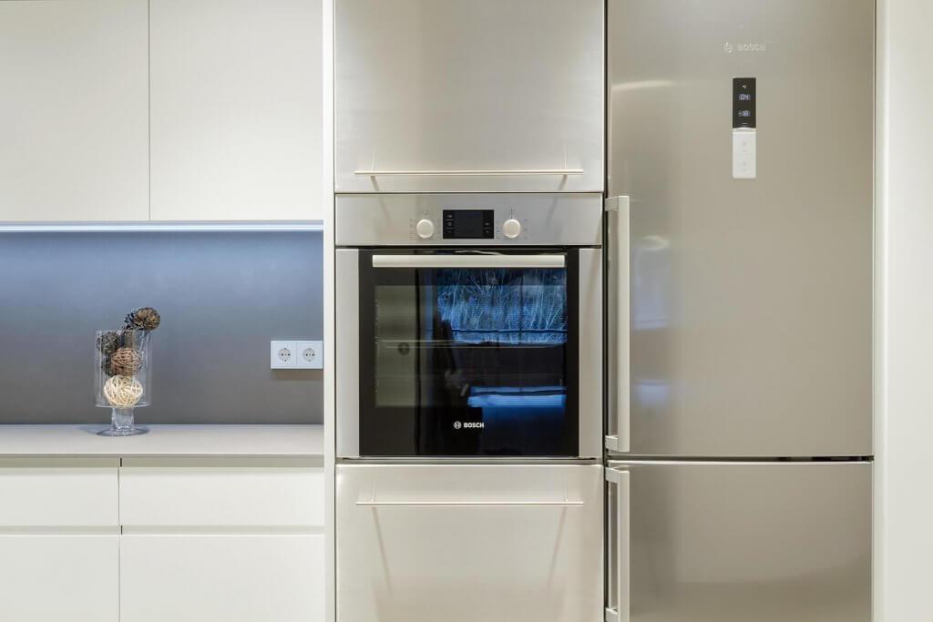 Detalle horno y nevera integrados en cocina lineal en tonos blanco y beige