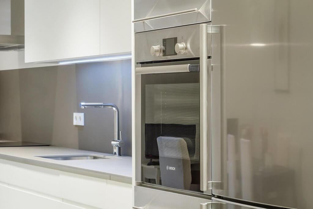 Detalle horno y nevera de cocina lineal con un solo frente en tonos blanco y beige