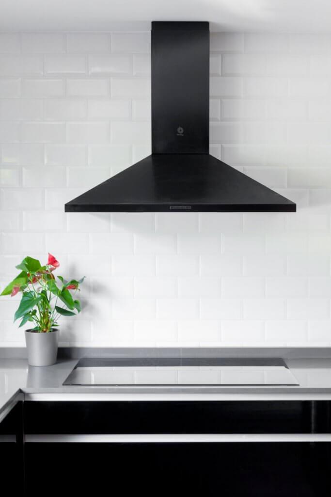 Cocina estratificada negra con isla con campana negra