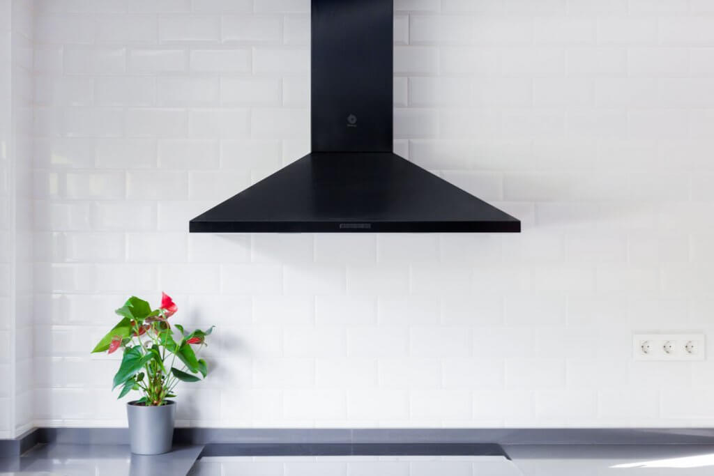 Cocina estratificada negra con isla, detalle de campana negra