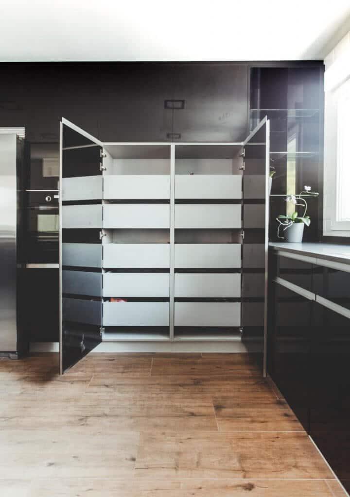 Cocina con isla con muebles negros estratificados