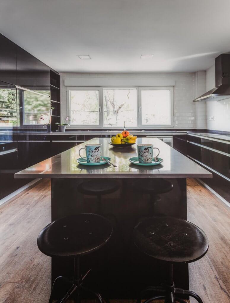 Cocina estratificada negra con isla con dos taburetes