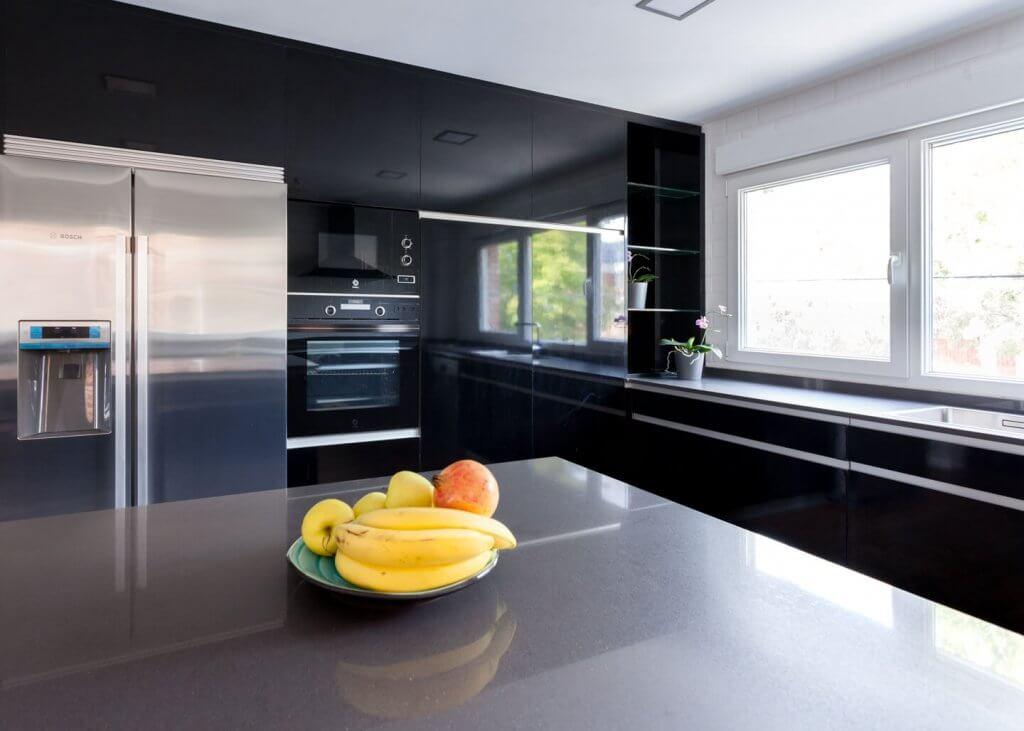 Cocina negra con isla electrodomésticos empotrados