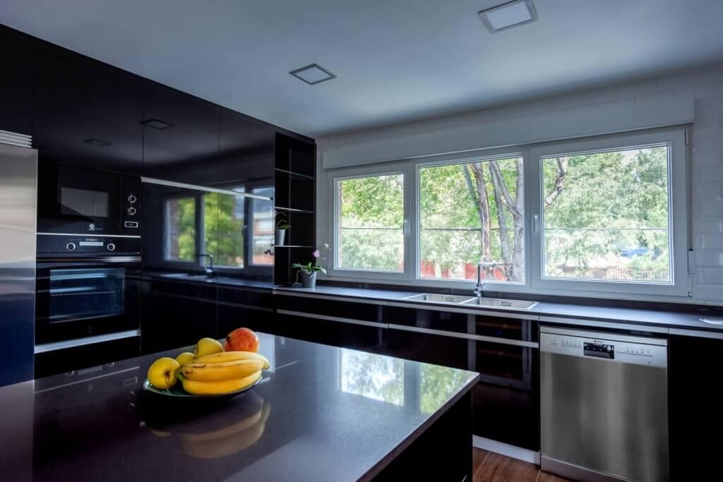 Cocina estratificada negra con isla electrodomésticos empotrados