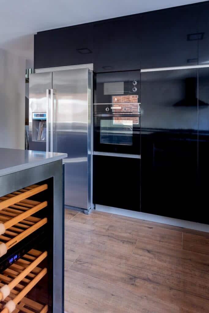 Cocina estratificada negra con isla con muebles empotrados y vinoteca