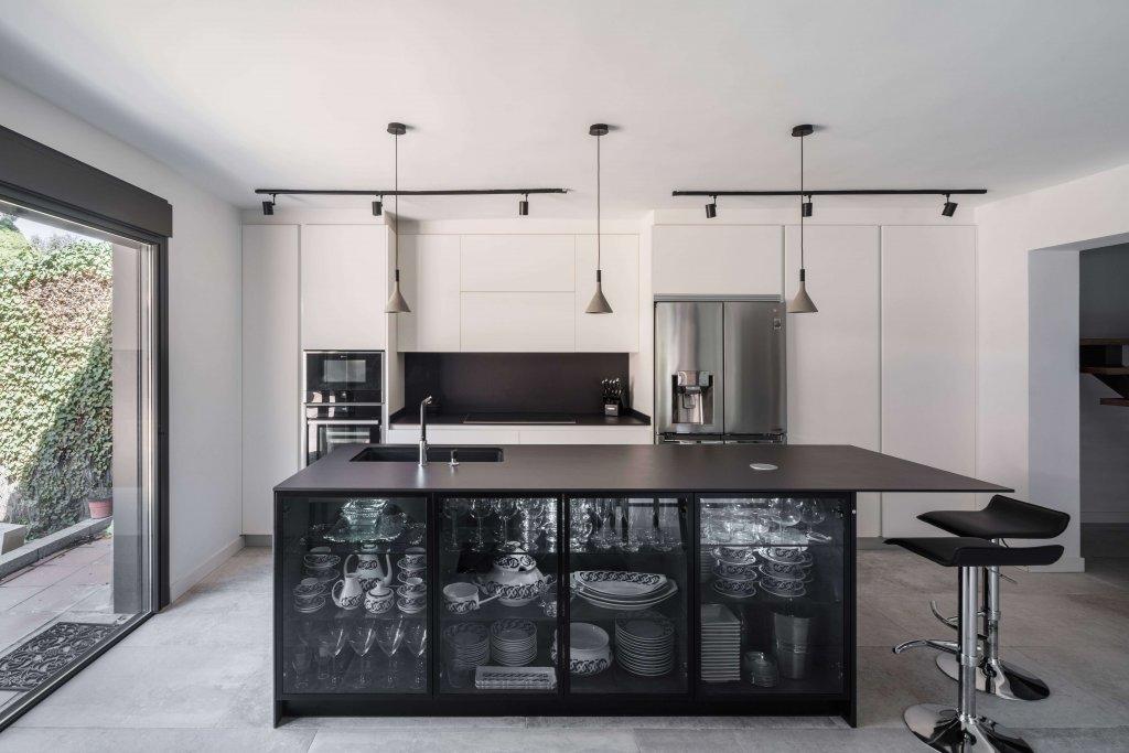 Cocina con isla con vitrina de diseño y taburetes