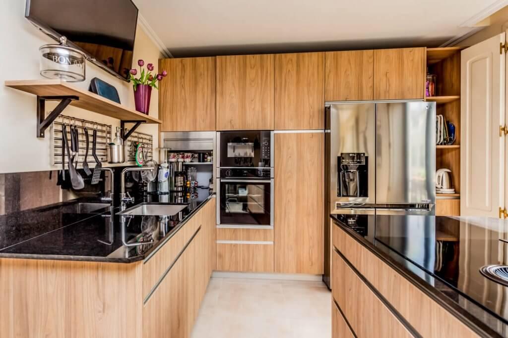 Cocina con isla en tonos de madera vista lateral