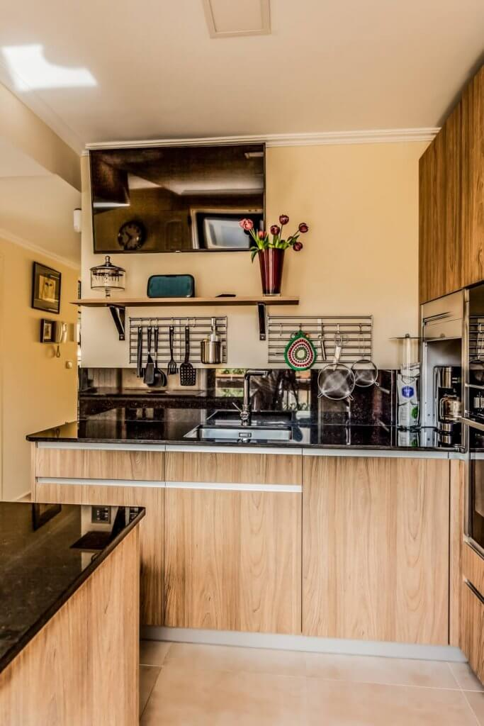 Cocina con isla en tonos de madera con televisión arriba en el techo