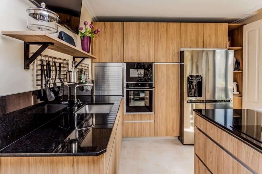 Cocina con isla en tonos de madera con muebles hasta el techo
