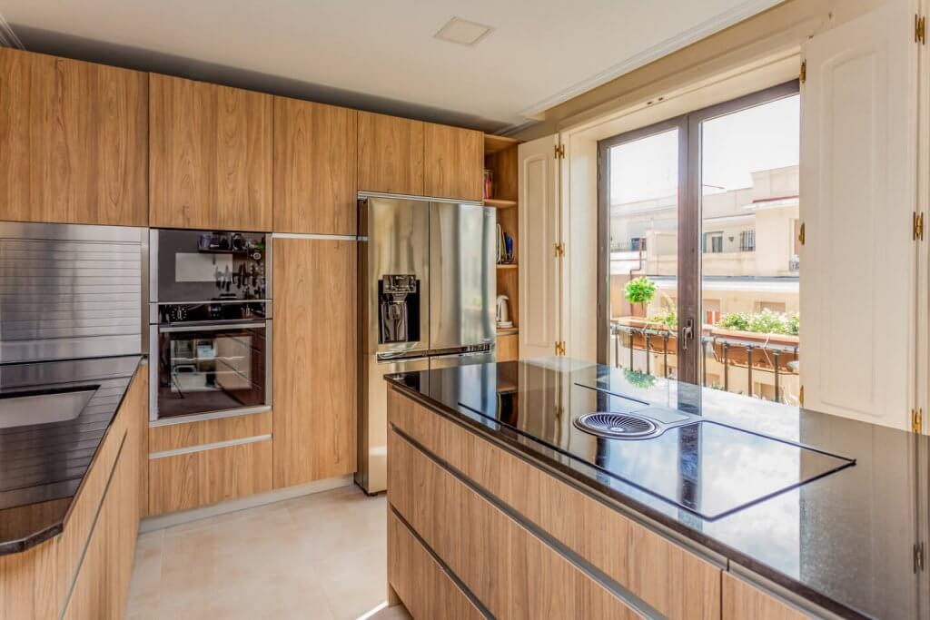 Cocina con isla en tonos de madera con el fondo al balcón