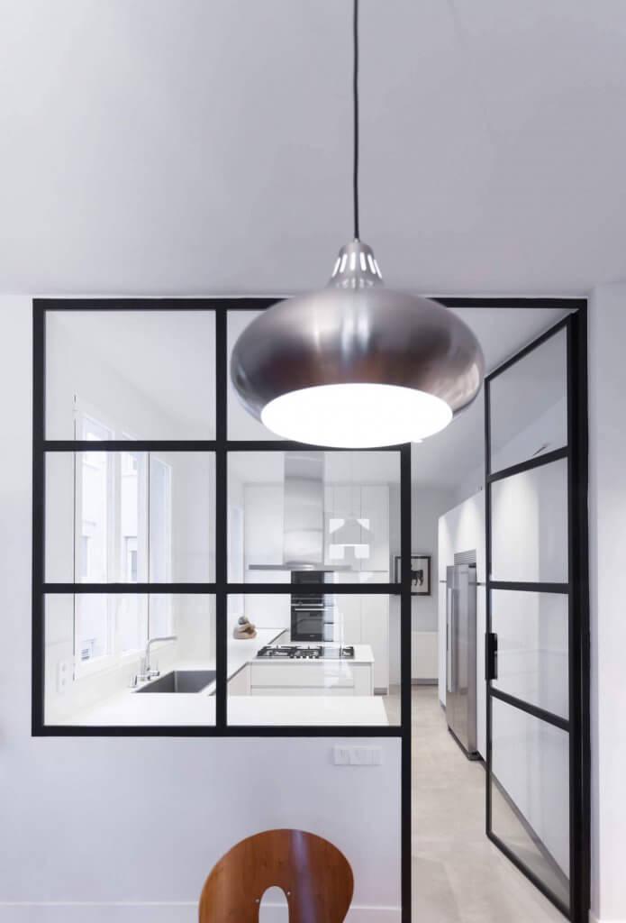 Puerta de entrada a cocina blanca con península