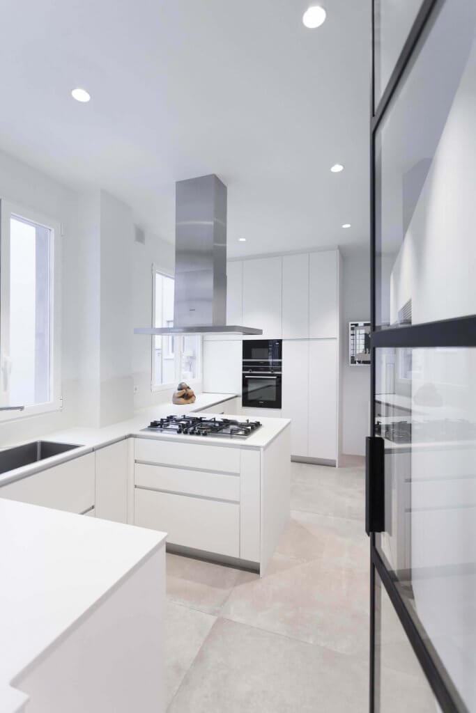 Entrada a cocina blanca con península