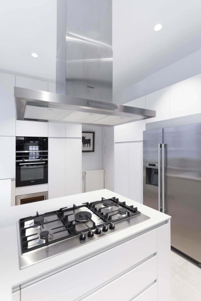 Cocina blanca con pequeña península con fuegos, nevera empotrada de fondo