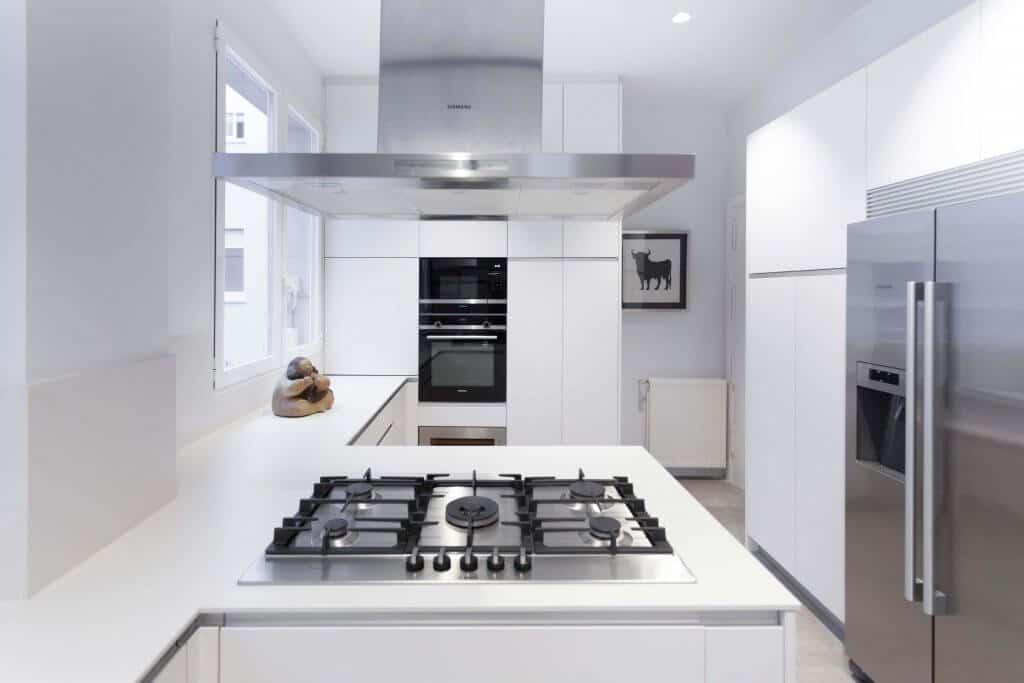 Cocina blanca con pequeña península con fuegos y campana metálica