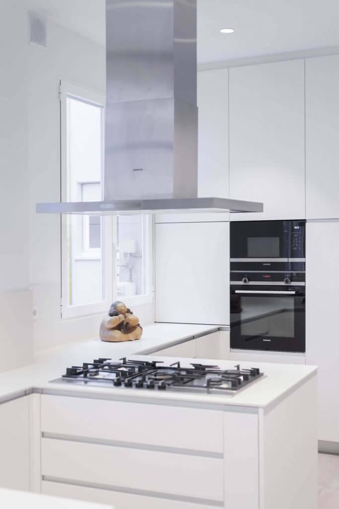Cocina blanca con pequeña península y campana metálica