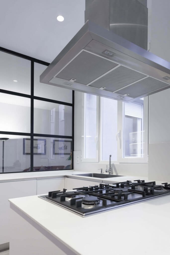 Campana de diseño metálica de cocina blanca con península