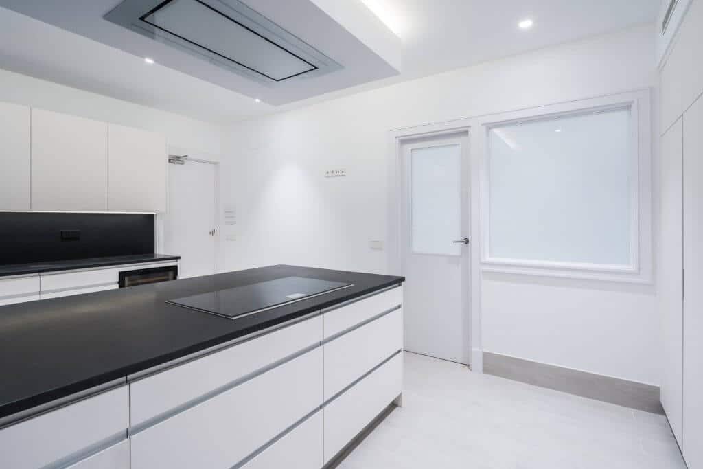 Cocina blanca con encimera negra