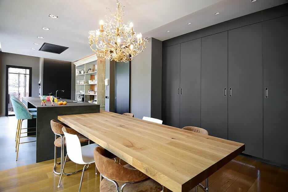 Cocina con isla oscura con mesa de madera