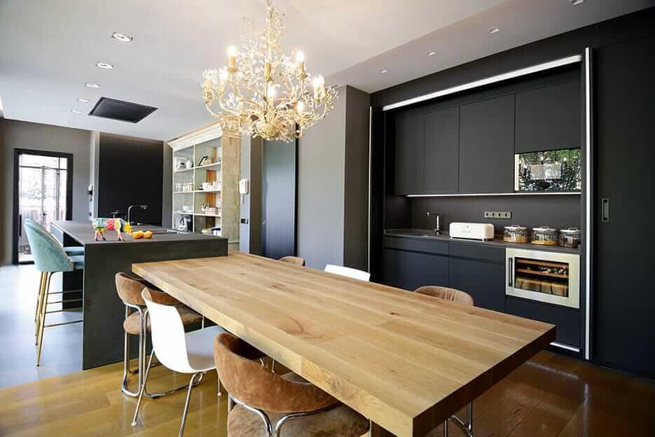 Cocina con isla en tonos oscuros con mesa de madera