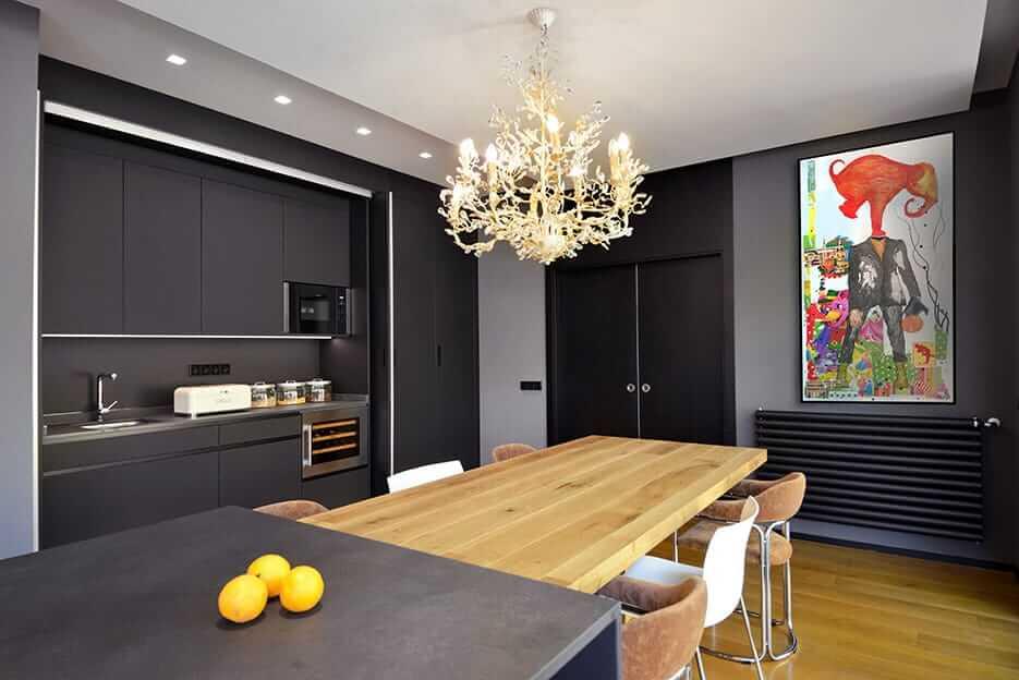 Cocina con isla en tonos oscuros, armario folding concepta y lámpara de araña encendida