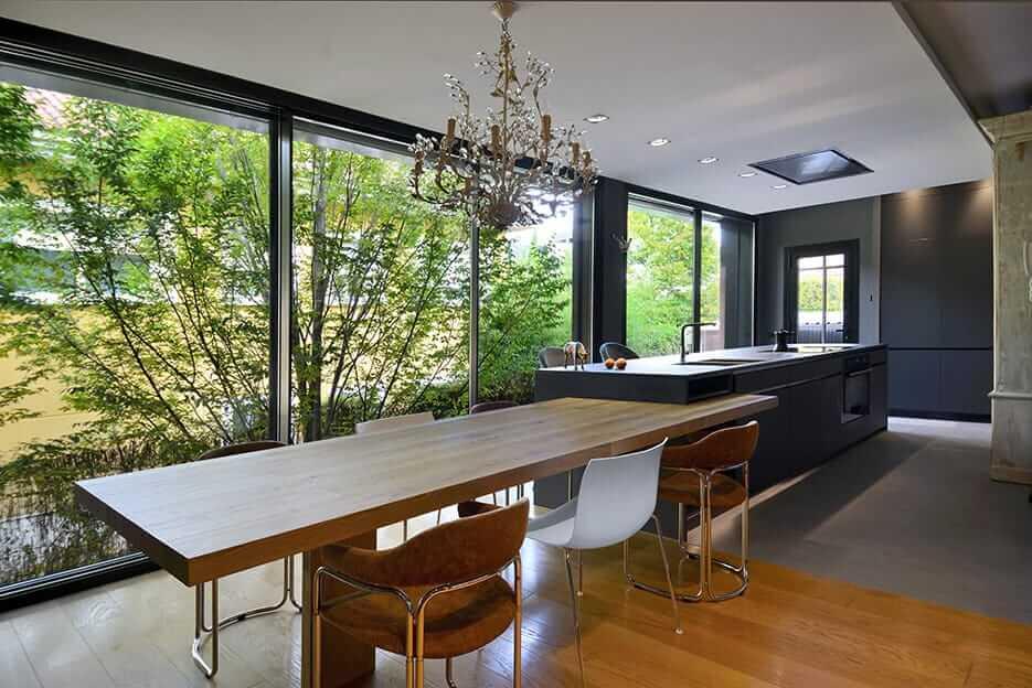 Cocina con isla en tonos oscuros, armario folding concepta y lámpara de araña