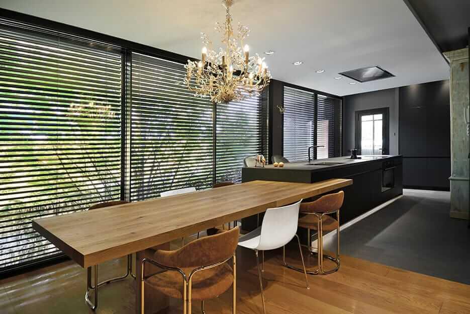 Cocina con isla en tonos oscuros con mesa de madera y persianas negras