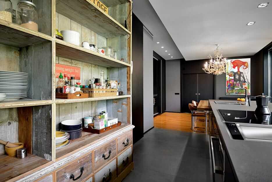 Cocina con isla en tonos oscuros con mesa de madera y contraste con armario antiguo