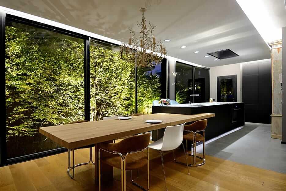 Cocina con isla en tonos oscuros con mesa de madera y ventanales grandes con vistas