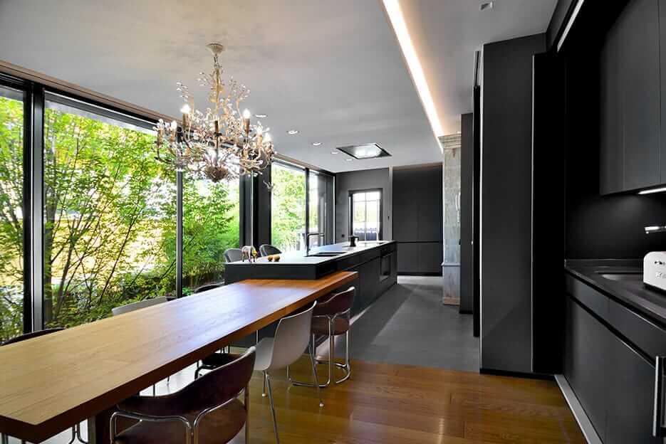 Cocina con isla en tonos oscuros con mesa de madera y lámpara de araña