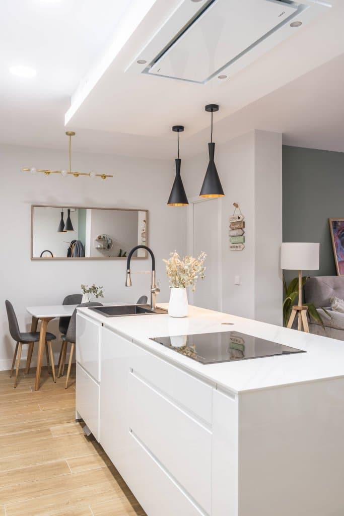 Cocina con isla estratificada blanca campana en el techo