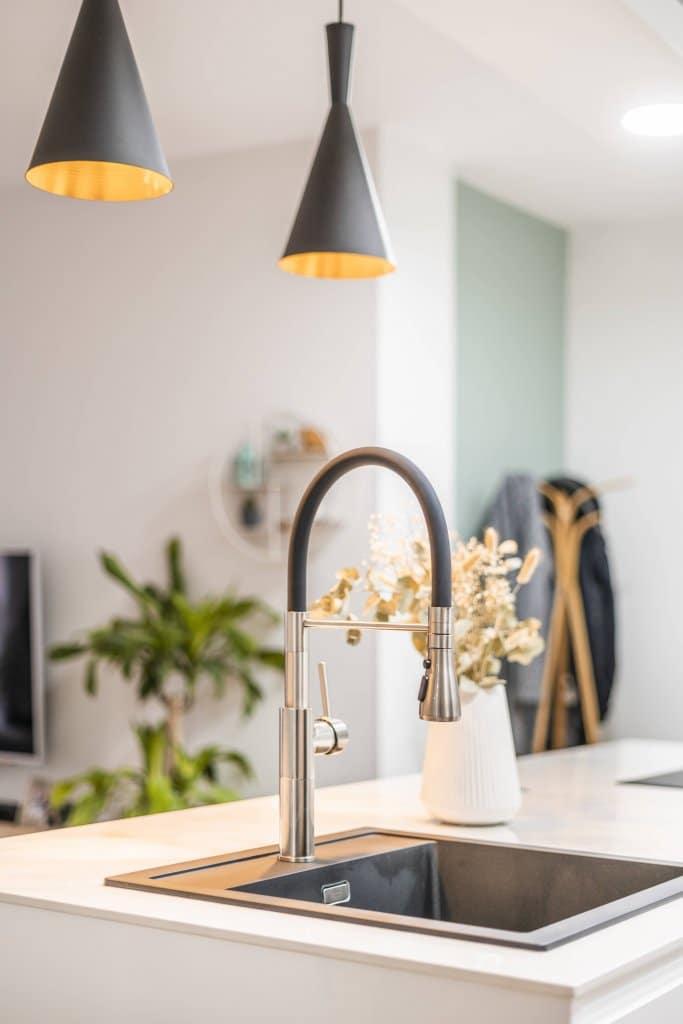 Cocina con isla estratificada blanca detalle lámparas