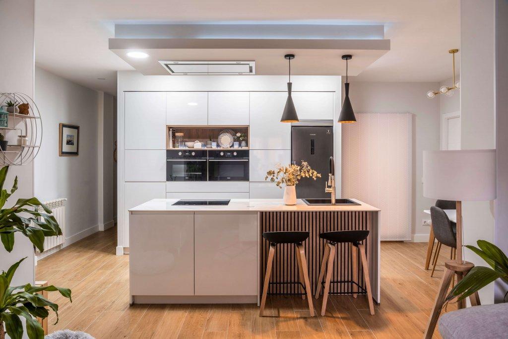 Cocina con isla estratificada blanca y panel de madera